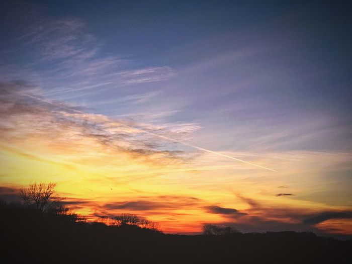 Low angle view of silhouette landscape against sky during sunset