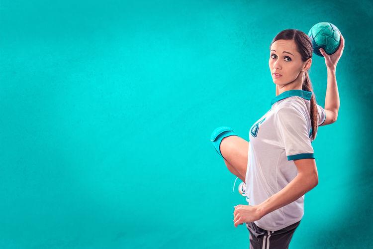 Sportswoman Holding Ball Against Blue Background