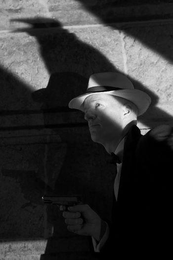 Mafia Holding Handgun Against Shadow On Wall
