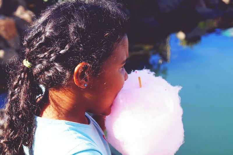 Close-up of girl eating cotton candy