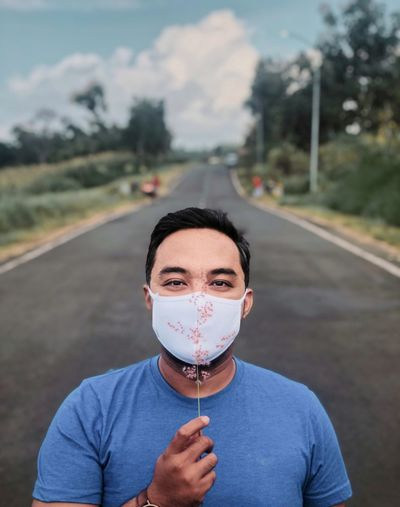 Portrait of man holding flower and wearing mask on road
