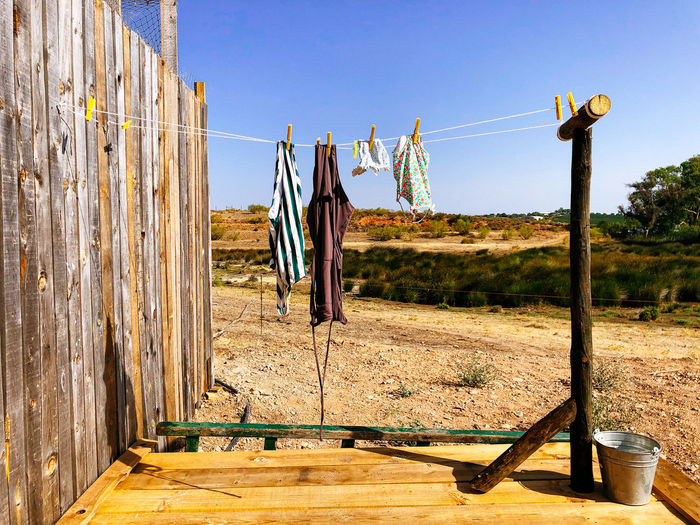 Clothes drying on wooden post against clear sky
