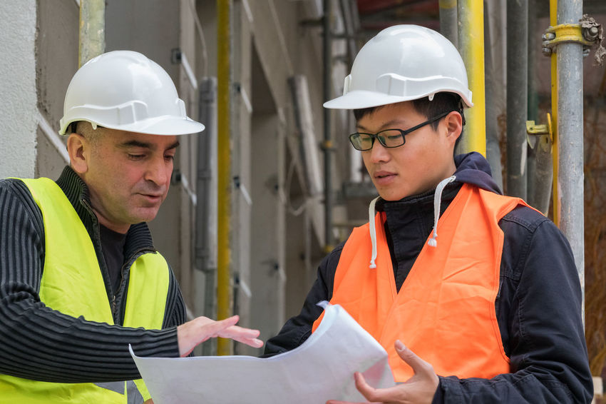 Construction site manager working with his young Asian apprentice Construction Site Apprenticeship Engineer Engineering Hardhat  Headwear Helmet Men Occupation Protective Workwear Real People Reflective Clothing Standing Team Teamwork Trainee Working