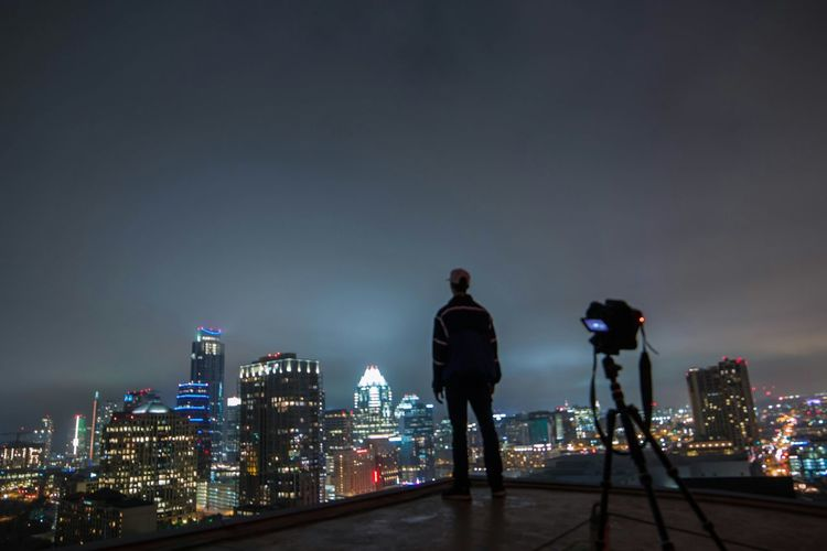 Rear View Of A Man Overlooking Illuminated Cityscape