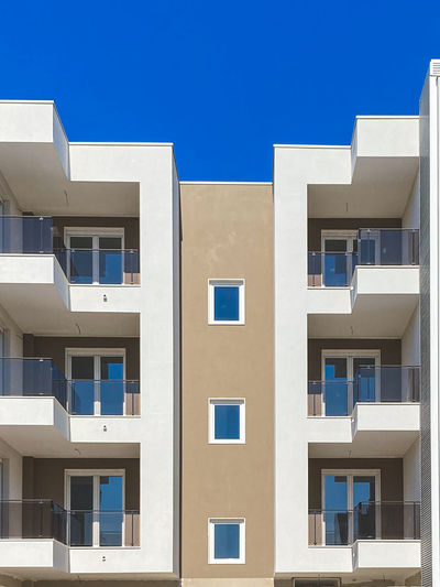 Low angle view of residential building against clear blue sky