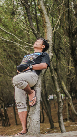 Low angle view of man leaning against tree trunk