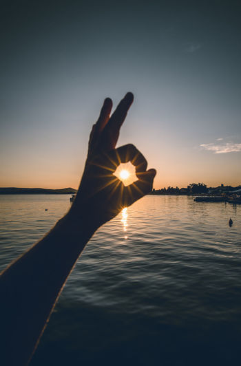 Person hand holding sea against sky during sunset