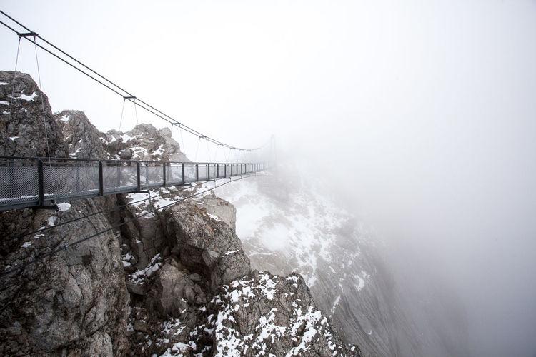 Narrow footbridge against rocky mountains