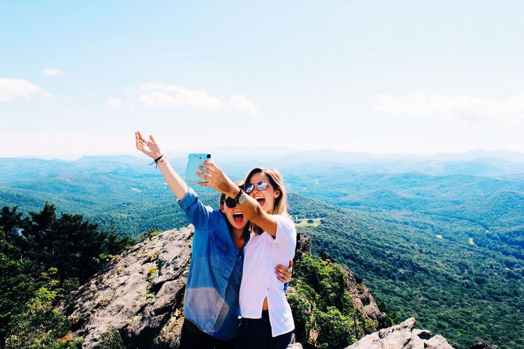 Young women taking selfie on mountain against sky