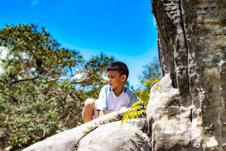 Cute boy sitting on rock formation against blue sky