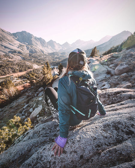 Hiking in the Eastern Sierras of California. Mountain Real People One Person Lifestyles Leisure Activity Mountain Range Beauty In Nature Sitting Rear View Full Length Scenics - Nature Women Solid Rock Sky Nature Non-urban Scene Rock - Object Tranquility Outdoors Hairstyle Warm Clothing