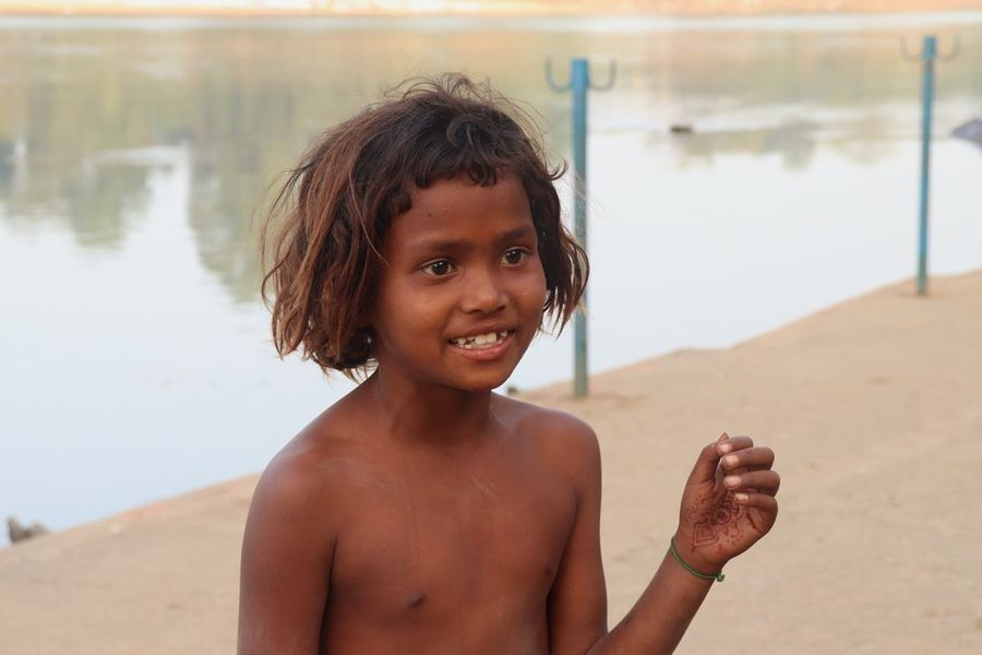 indian lil girl EyeEm Selects Portrait One Person Looking At Camera Beach Real People Childhood Lifestyles Front View Leisure Activity Day Focus On Foreground Hairstyle Innocence Land Shirtless Smiling Child Water