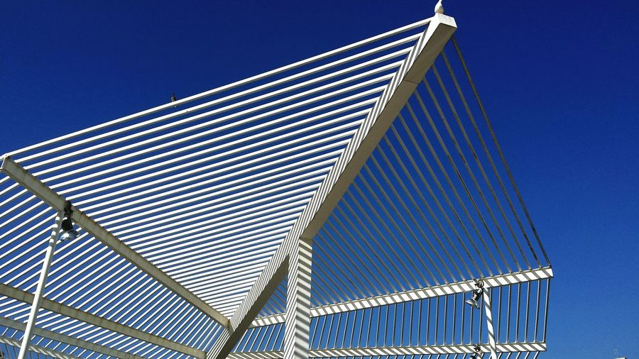 Low angle view of modern structure against blue sky