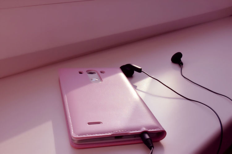 Close-up of mobile phone with in-ear headphones