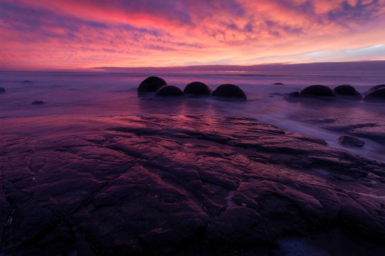 Moeraki Boulders Beauty In Nature Cloud - Sky Idyllic Land Nature No People Non-urban Scene Orange Color Rock Rock - Object Rock Formation Scenics - Nature Sea Sky Solid Sunset Tranquil Scene Tranquility Water