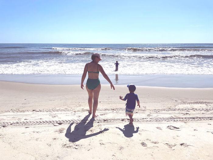 Full length of boys on beach against sea