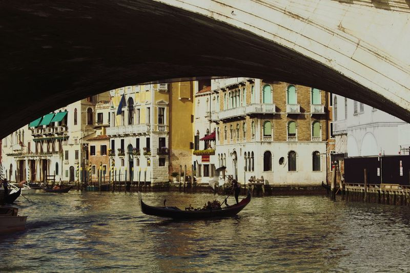 Gondolier in gondola at grand canal seen from arch of rialto bridge