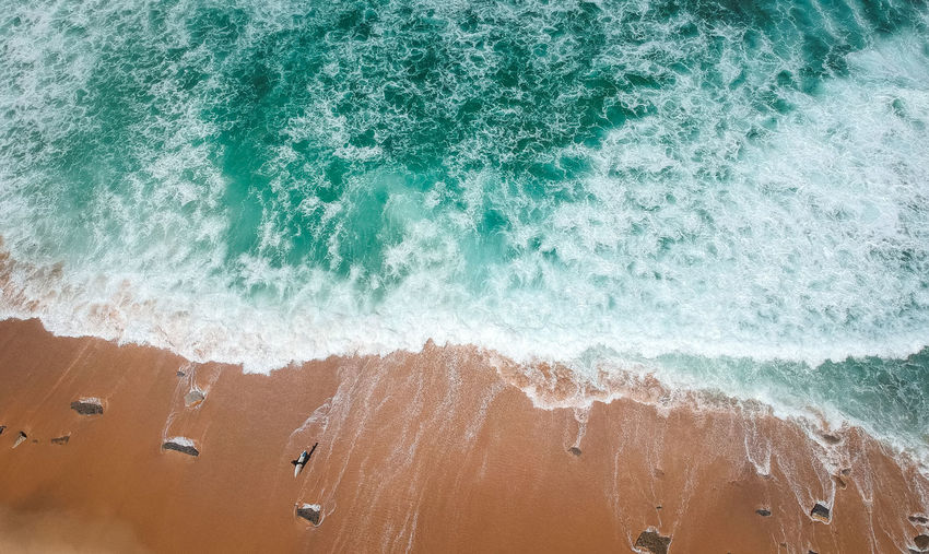 High angle view of waves splashing on beach