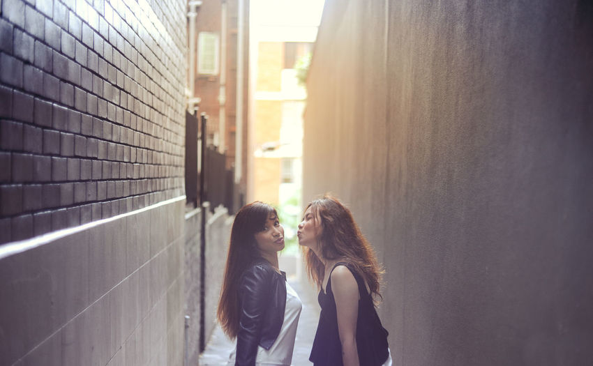 Portrait Of Woman Standing With Female Friend Puckering At Alley
