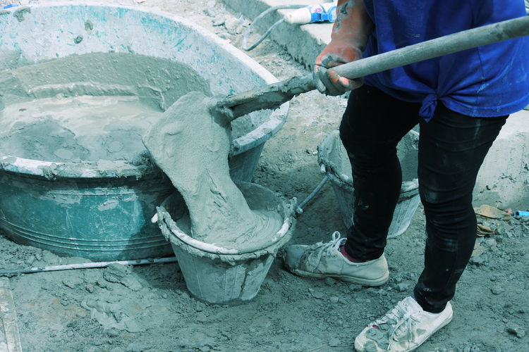 Low section of woman pouring concrete in bucket at construction site