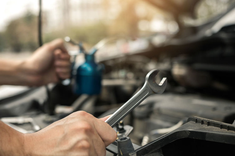 Cropped image of person repairing car engine