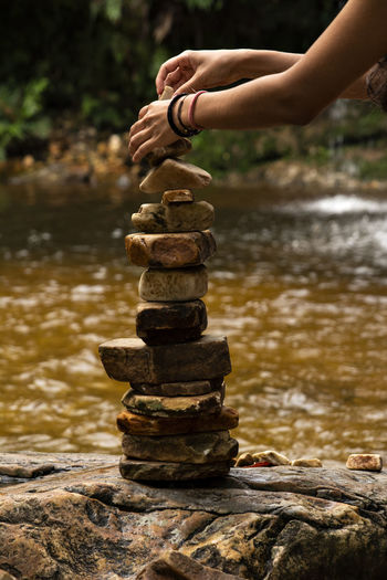Cropped hands stacking stones by river