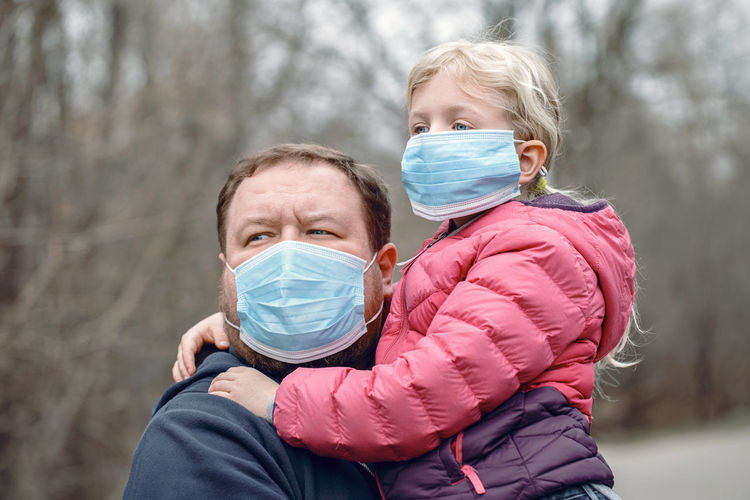 Father and daughter wearing flu mask looking away standing outdoors