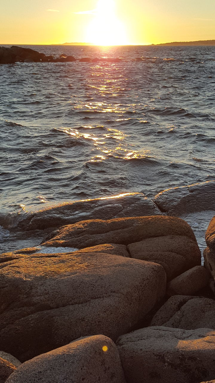 Rocks At Seashore During Sunset