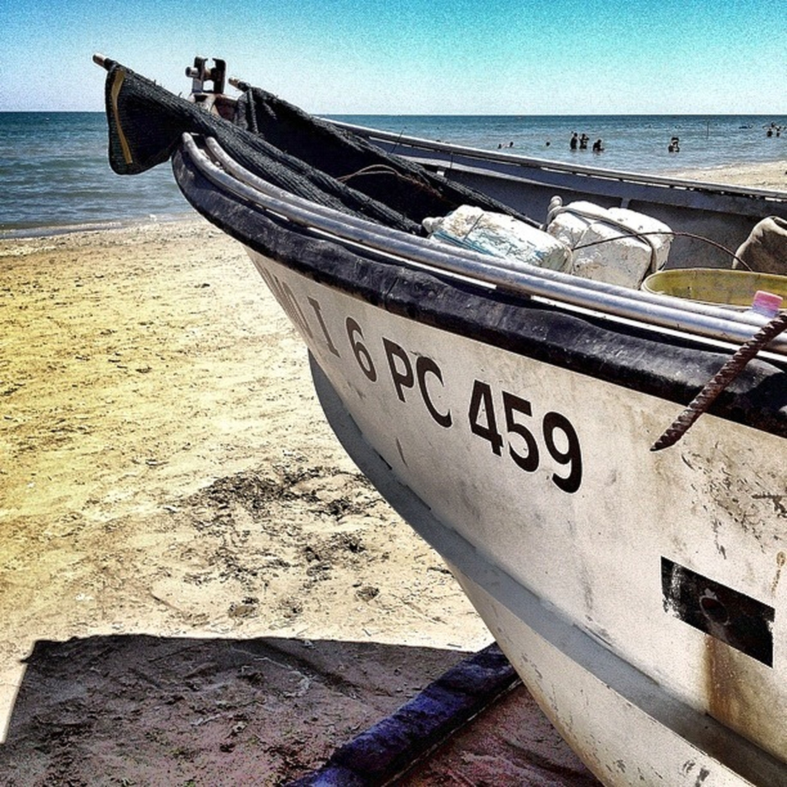 sea, beach, water, horizon over water, shore, sand, text, nautical vessel, tranquility, western script, tranquil scene, transportation, nature, boat, mode of transport, sky, scenics, outdoors, clear sky, beauty in nature