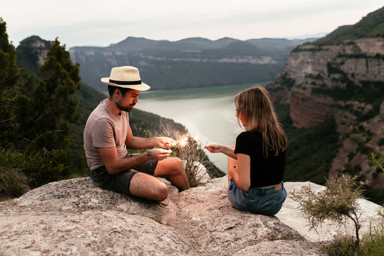 People sitting on rock by mountains