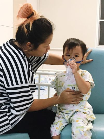 Mother Sitting By Son Using Oxygen Mask While Sitting In Hospital