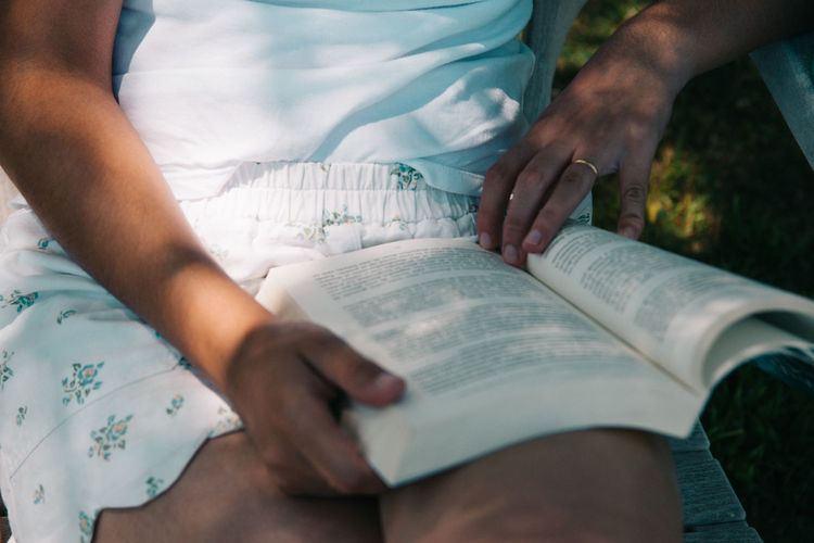 Midsection of woman reading book