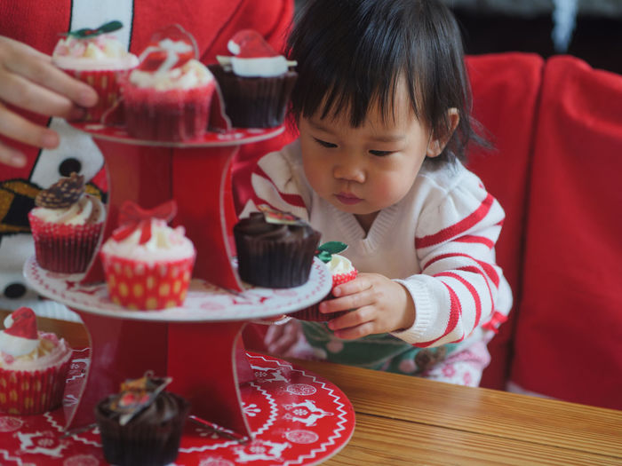 Baby girl having cupcake at table
