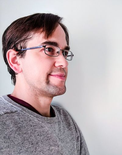 Friendly Young Man with Glasses, Unshaven Looking Into The Future People Happy Friendly Smiling Unshaven Whiskers Copy Space Interior Unkept Brown Hair Caucasian Young Adult Young Man Male Young Affable Looking Away Portrait Eyeglasses  Studio Shot Headshot Human Face White Background Mid Adult Straight Hair Head And Shoulders Glasses Hair Toss