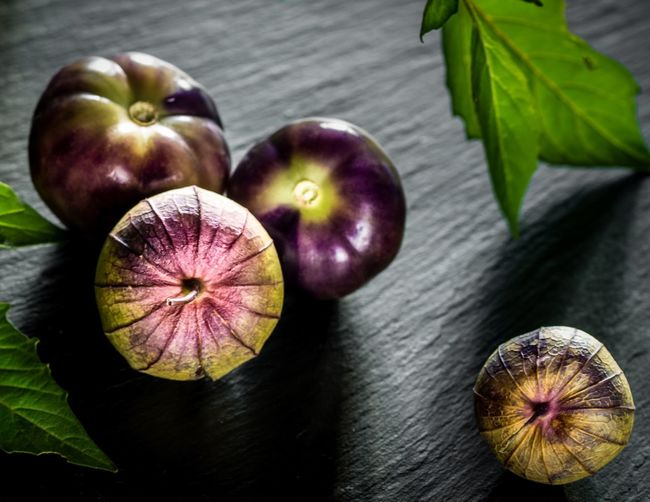 Close-Up Of Purple Tomatillo On Wooden Table