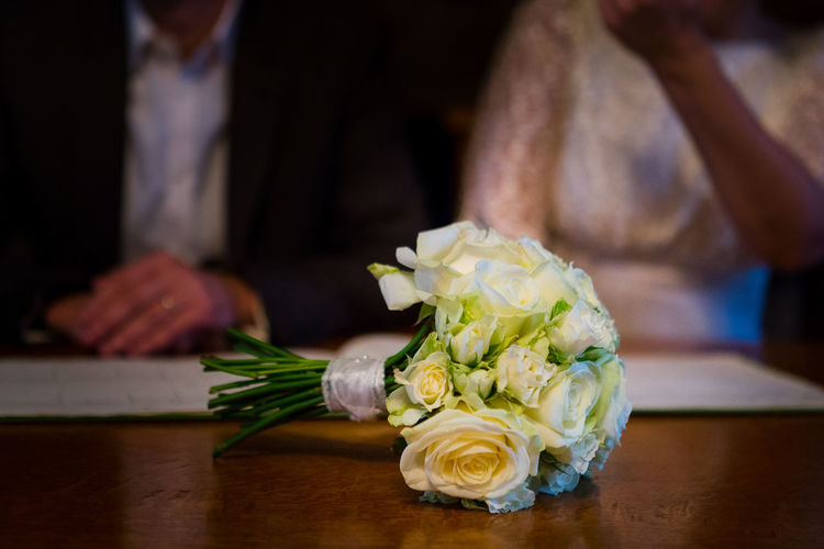 Close-Up Of White Roses Bouquet With Bride And Groom In Background