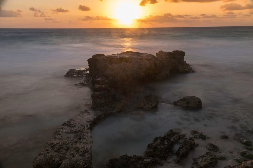 Isla mujeres mexico, a hidden beauty just off the coast of cancun. Day one of this place left me excited and at 4 am with jet lag and to much heat to sleep, I slipped out with the camera and captured this image of the rising sun and the beautiful sea in its glory as the sun ascended into the day sky, my love of the island grew stronger for its true beauty was their for all to see Sunset Sea Beauty In Nature Nature Water Scenics Sun Sky Horizon Over Water Rock - Object Tranquility Tranquil Scene Beach Idyllic Outdoors No People Motion Wave Day