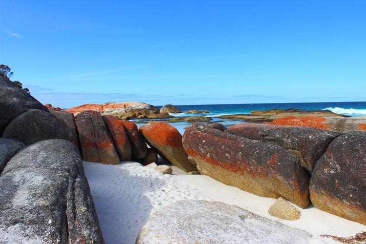 Rocks by sea against blue sky