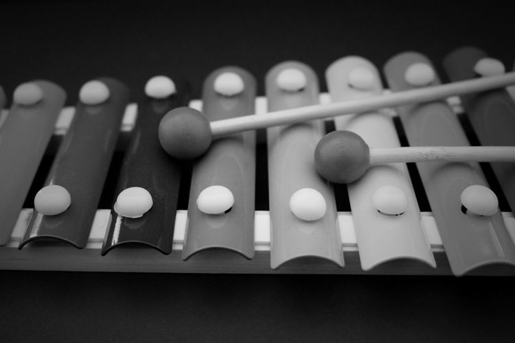 Close-up of mallets with xylophone against black background