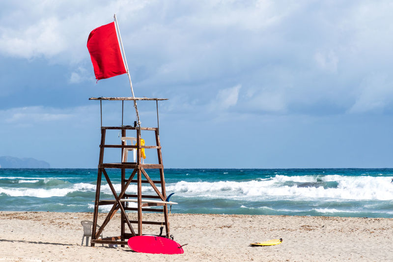 Krull&Krull Images Mallorca Beach Beauty In Nature Cloud - Sky Day Flag Horizon Over Water Life Guard Nature No People Outdoors Red Sand Scenics Sea Sky Son Serra De Marina Stormy Tranquil Scene Tranquility Water Wave An Eye For Travel Summer Exploratorium