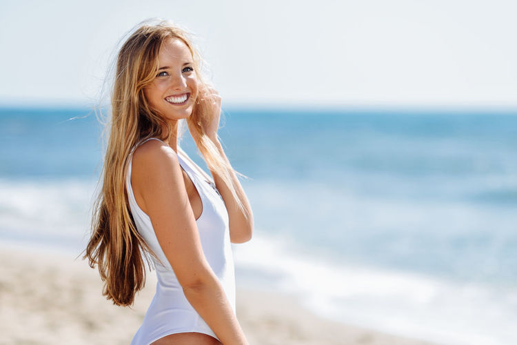 Side view portrait of beautiful woman standing at beach