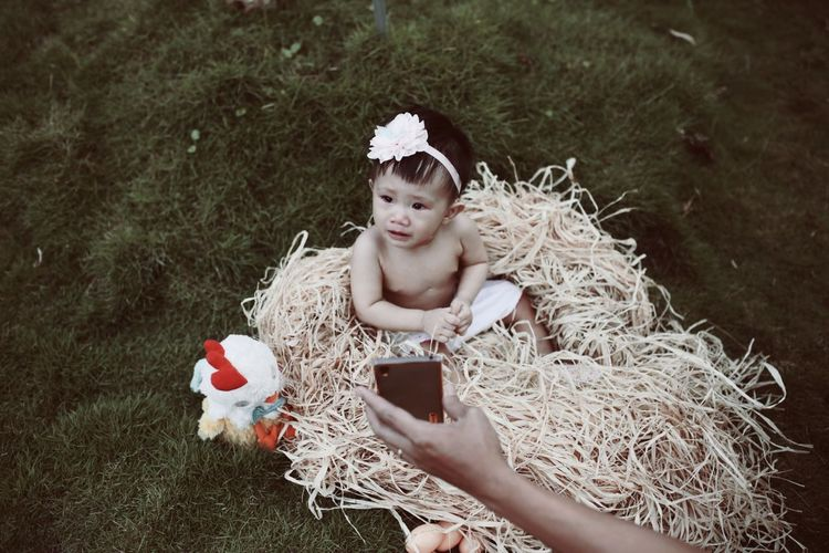 High angle view of topless baby girl sitting on straw at field