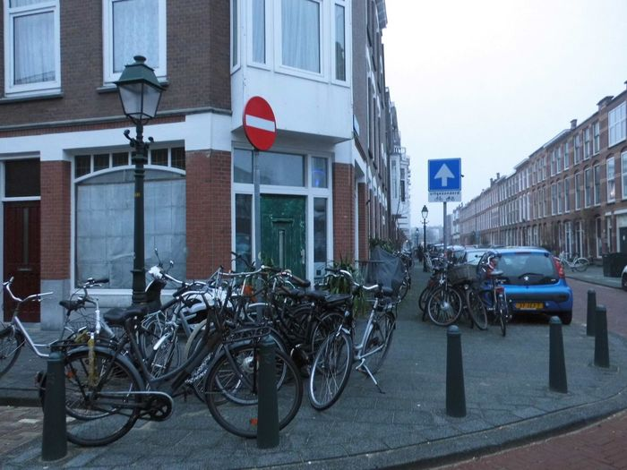 Bicycles parked on street against buildings in city