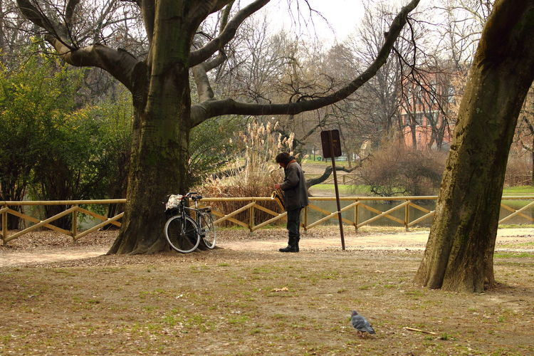 Street performer playing saxophone in a park Absence Alone Carefree Day Emotional Escapism Getting Away From It All No Filter Outdoors Parco Sempione Park Streetphotography Transportation