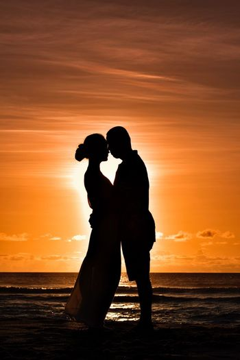 Silhouette couple embracing at beach against orange sky during sunset