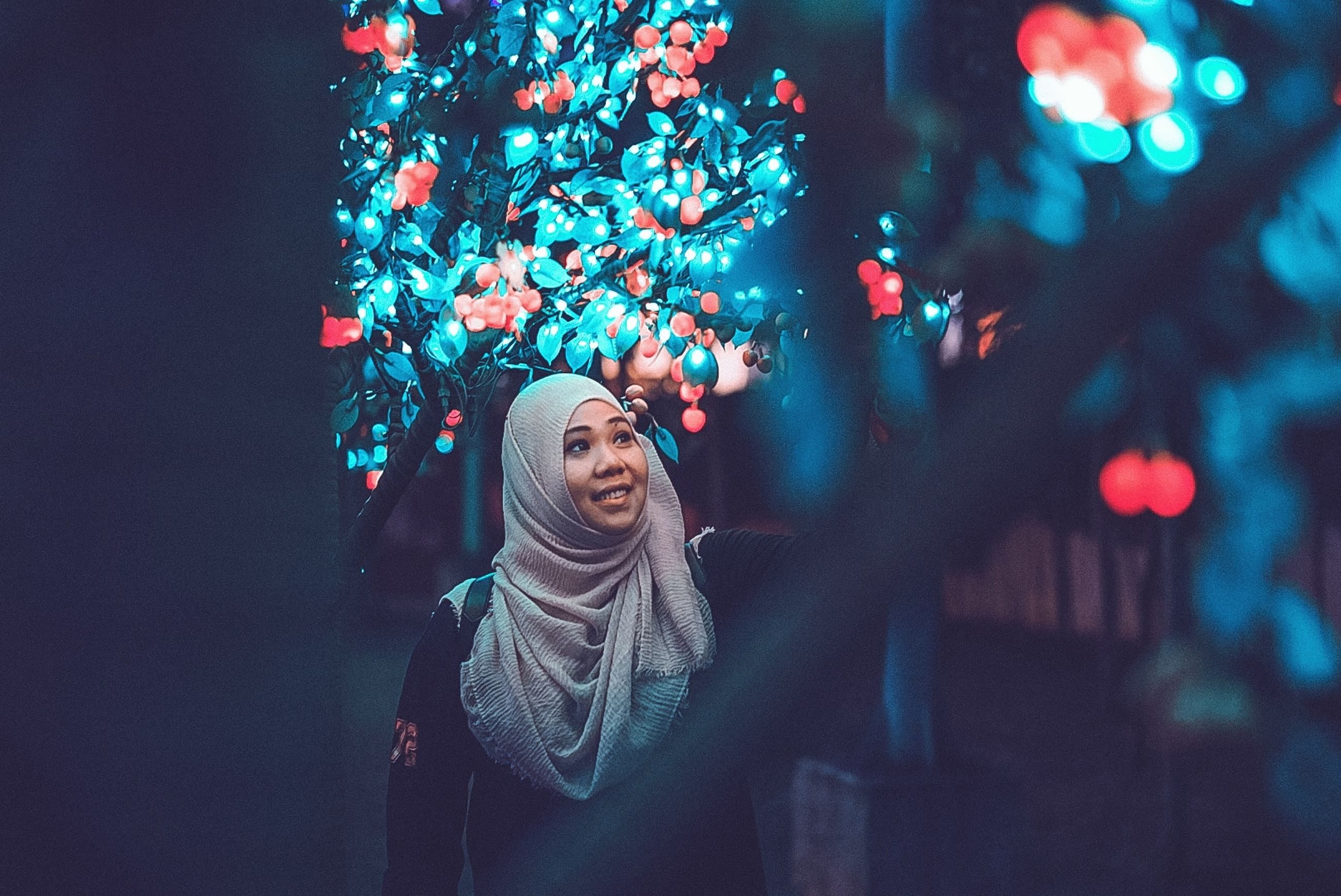 tree, christmas, celebration, holiday, illuminated, christmas decoration, plant, night, one person, decoration, christmas tree, young women, lifestyles, real people, clothing, looking, young adult, winter, christmas lights, warm clothing, scarf, outdoors, christmas ornament