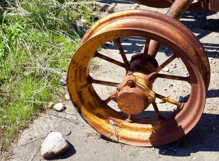 Close-up of rusty wheel on field