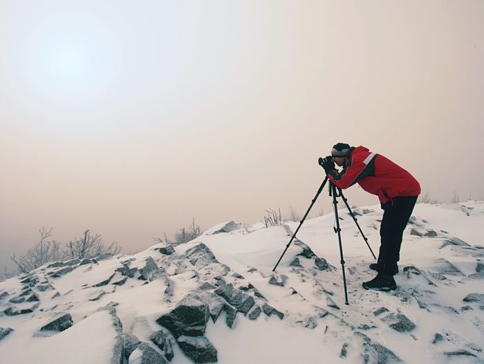 Photographer takes picture of freeze autumnal daybreak, rocks covered with fresh powder snow.