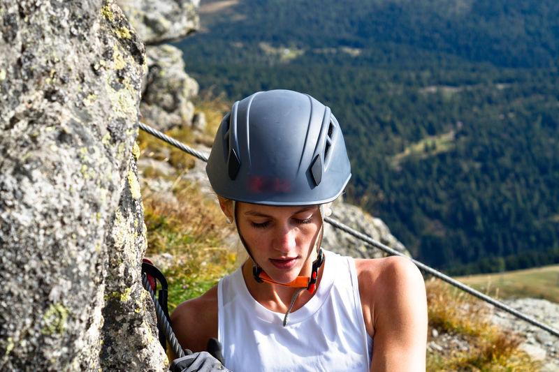 Portrait of woman climbing rock on mountain