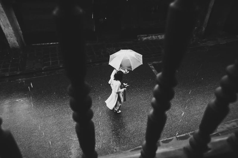 High Angle View Of Man And Woman In Umbrella Walking On Street In Rainy Season